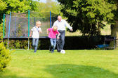Grandfather with grandsons playing soccer in the garden — Stock Photo
