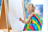 Preschooler girl drawing on paper roll — Stock Photo