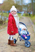 Little girl walking with stroller in the park — Stock Photo