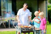 Father and sons preparing barbecue for summer party — Stockfoto