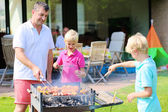 Father and sons preparing barbecue for summer party — Stock Photo
