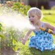 Cute little girl watering flowers in the garden — Stock Photo #68115293