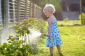 Cute little girl watering flowers in the garden — Stock Photo
