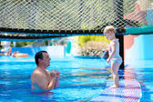 Father and daughter playing in swimming pool — Stock Photo