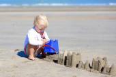 Cute girl building sand castles on the beach — Stock Photo