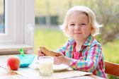 Little girl having toast and milk for breakfast — Stock Photo