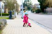 Little child playing on the street riding tricycle — Foto Stock