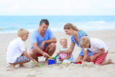 Happy family enjoying summer vacation on the beach — Stockfoto