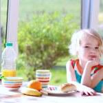 Funny girl enjoying healthy breakfast — Stock Photo #70841325
