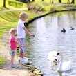 Brother and sister feeding birds in the pond — Stock Photo #70841769