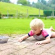 Preschooler girl drawing with chalk outdoors — Stock Photo #70842739