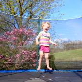Cute toddler girl jumping on trampoline — Stock Photo