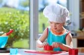 Happy toddler girl preparing cookies — Stock Photo