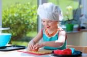 Happy toddler girl preparing cookies — Stock Photo