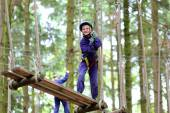 Happy school boy climbing in adventure park — Stok fotoğraf