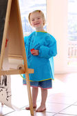 Cute little girl painting with brushes indoors — Stock Photo