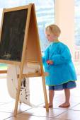 Cute little girl painting with brushes indoors — Stockfoto