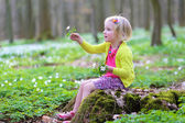 Adorable little girl enjoying spring blooming forest — Stock Photo