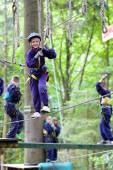 Happy school boy climbing in adventure park — Fotografia Stock