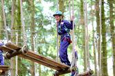 Happy school boy climbing in adventure park — Foto de Stock