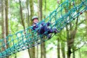 Happy school boy climbing in adventure park — Stock Photo