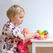 Toddler girl playing with dolls indoors — Stock Photo
