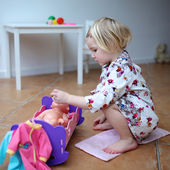 Toddler girl playing with dolls indoors — Foto Stock