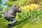 Happy senior man enjoying flowers park — Stock Photo