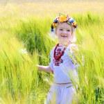 Little girl in Ukrainian dress playing in the field — Stock Photo #73982061