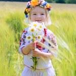 Little girl in Ukrainian dress playing in the field — Stock Photo #73982075