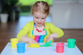 Preschooler girl drawing with finger paint — Stock Photo