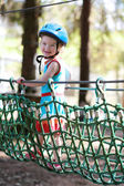 Happy child, healthy toddler preschool age girl enjoying activity in a climbing adventure park on a summer day — Stockfoto