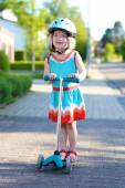 Preschooler girl riding scooter on the street — Stock Photo