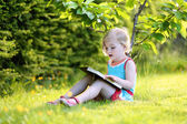Smart preschool age girl reading book in the park — Stock Photo