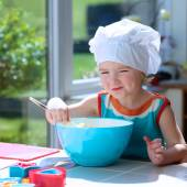 Cute little girl baking pastry in the kitchen — Stock Photo