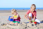 Brother and sister playing on the beach — Stock Photo