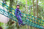 Active school boy climbing in adventure park — Stock Photo