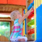 Little girl having fun at playground on summer day — Stock Photo