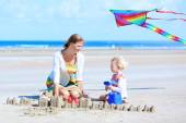 Mother and daughter playing on the beach — Stock Photo