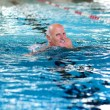 Постер, плакат: Active senior man swimming in the pool