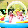 Kids enjoying inflatable swimming pool on summer day — Stock Photo #79597616