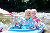 Two happy kids kayaking on the river — Stock Photo