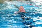 Active senior man swimming in the pool — Stockfoto