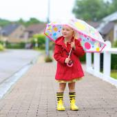 Portrait of playful little girl with colorful umbrella — Stock Photo