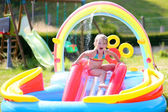 Little girl having fun in inflatable swimming pool — Stock Photo
