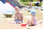 Kids playing with water and sand at summertime — Stock Photo