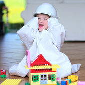 Toddler girl wearing safety helmet playing with building blocks — Stock Photo
