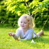 Little kid playing in garden lying in grass — Stock Photo