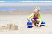 Little girl playing on the beach at summer — Stock Photo