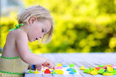 Preschooler girl playing outdoors in kindergarten — Stock Photo